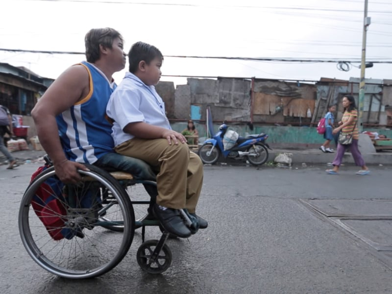 Photo Of A Father Driving His Son To School On A Wheelchair Went Viral