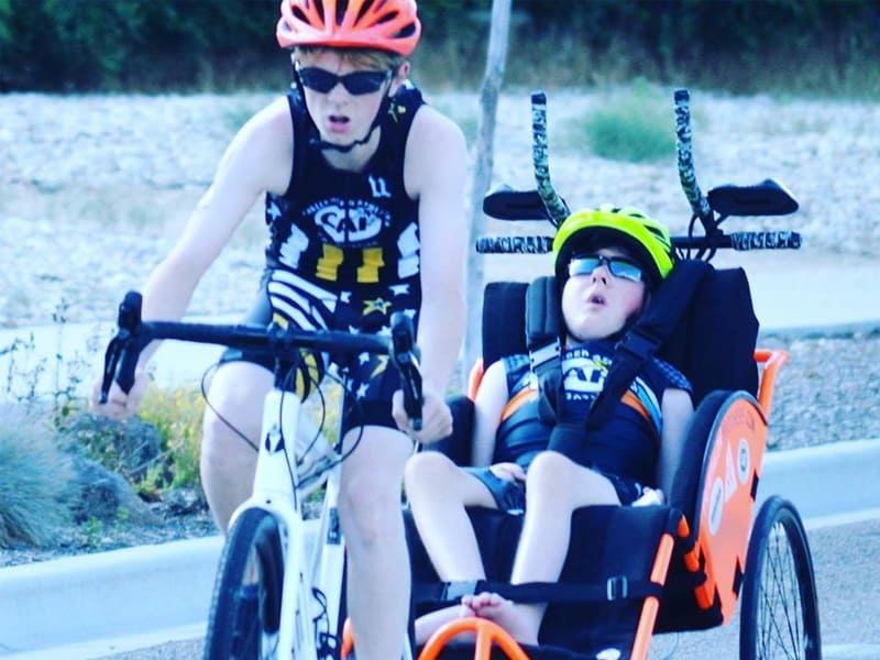 8-Year-Old Boy Hailed As Hero For Carrying His Disabled Brother Through A Triathlon