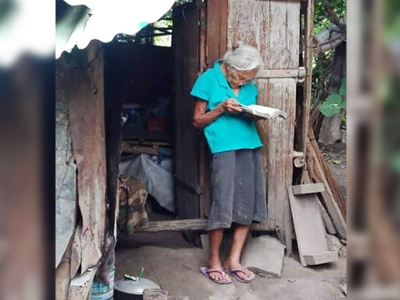 A Picture Of An Elderly Woman Reading Her Bible Outside Her Hut Stirs Hearts